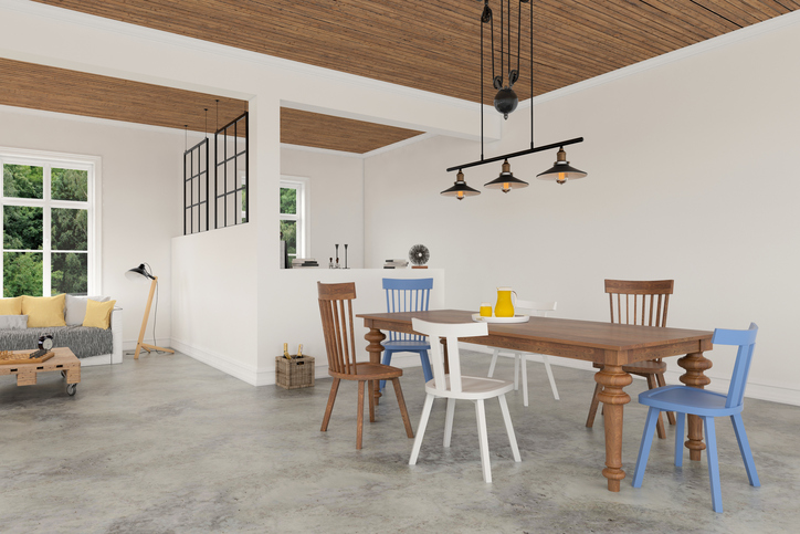 White apartment interior showing comfortable living room sofa on the left, and a wooden dining table with colorful chairs. There are windows showing green nature scenery. Concrete polished floor with wooden coffee table. Lots of decorative details. Horizontal composition